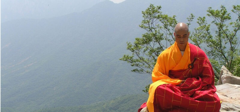 Монах на горе и голубой пейзаж
